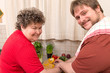 Leinwandbild Motiv Geistig behinderte Frau und junger Mann schneiden gemeinsam Gem