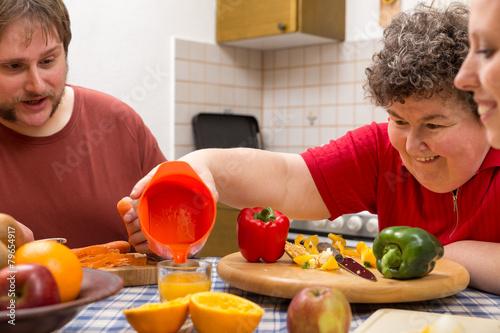 Geistig behinderte Frau mit Betreuern am Tisch mit viel Gemüse - 79654917