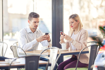 Two young business people sitting in a coffee shop