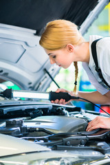 Female mechanic working in car workshop