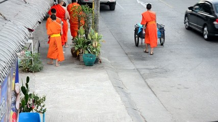Monk walking on the road for people pray and put food offerings