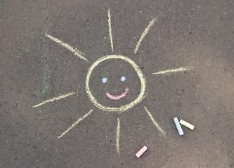 chalk drawn sun on asphalt