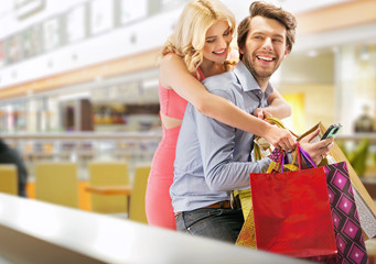 Young cheerful couple in the shopping mall