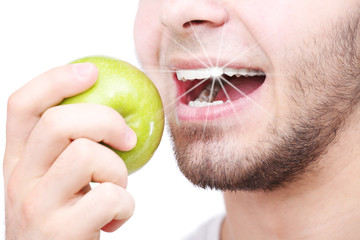 Man biting fresh green apple with healthy teeth isolated