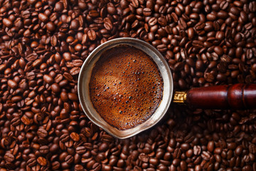 Hot coffee prepared in a Turk. Coffee beans background.