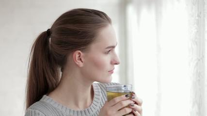 Young beautiful woman drinking green tea near window