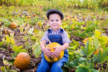 Little kid with pumpkin in hands
