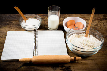 baking ingredients and cook book on table