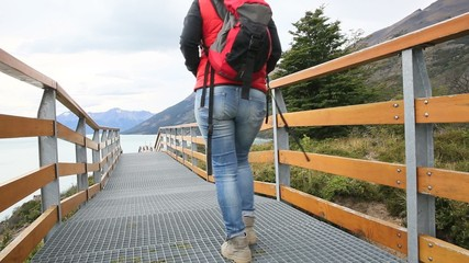 Tourist walking on Perito Moreno footbridge by Argentino lake