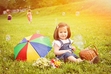 Smiling toddler girl on picnic in park in spring with sisters