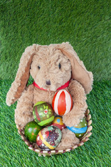 Rabbit, sit and holding colorful eggs in basket on grass for hap