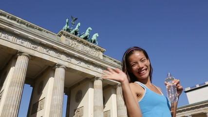 Woman waving hand saying hello running in Berlin