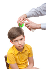 Man sprinkles boy's hair by medical spray