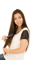 Happy Asian American young teen girl brushing her hair