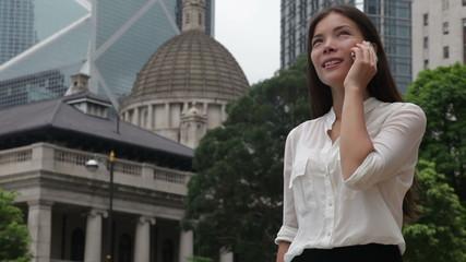Businesswoman talking on phone outdoor, Hong Kong