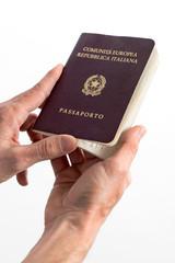 Hands of a man holding an Italian passport