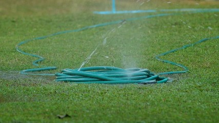 water hose rupture spraying water on the yard