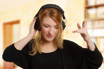 junge blonde Frau tanzt zu Musik auf Kopfhörern