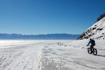 A cycler is riding on the ice of Baikal lake