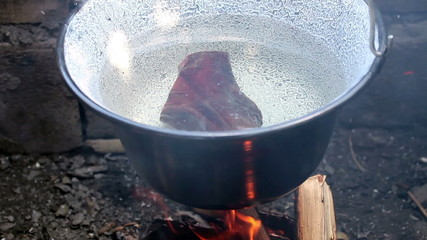 boiling water with meat  in a vintage kettle