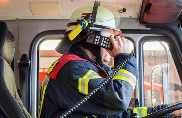 Feuerwehrmann im Einsatzfahrzeug beim funken