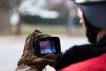 Feuerwehrmann mit Wärmebildkamera im Einsatz