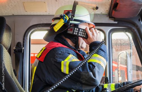 Feuerwehrmann im Einsatzfahrzeug beim funken - 79670714