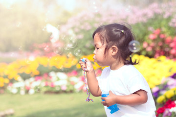 Cute little girl is blowing soap bubbles in flower garden in vin