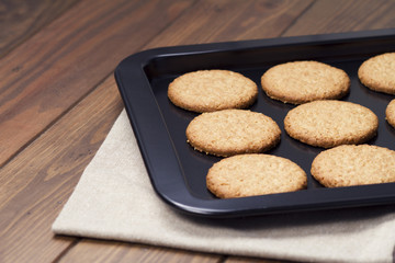 Biscuits freshly baked in a black baking tray. A wooden table