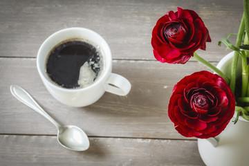 Vase mit Ranunkeln und Tasse Kaffee