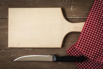Schneidbrett, Küchentuch mit Messer auf Holzuntergrund