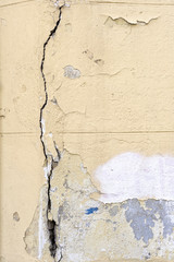 Close up of old cement wall with a crack and peeling wall