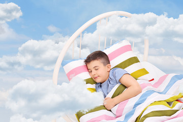 Little boy sleeping on a bed in the clouds