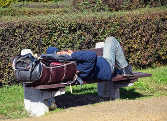 Homeless man is sleeping on a bench in the park