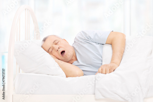 Mature man sleeping in a comfortable bed - 79673737