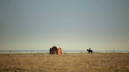 Horseman ride gallop on black horse to little church across the