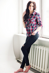Young attractive woman in squared shirt posing in studio. Casual