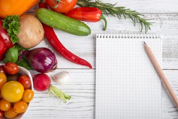 Ein Schreibblock mit Bleistift auf Holz, Gemüse, Kräuter