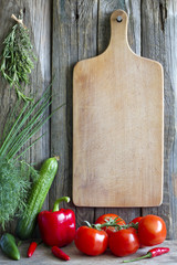 Old empty cutting board and vegetables background concept