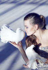 Gentle portrait of a beautiful girl with a white dove, over  a s