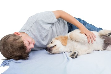Boy lying with puppy on blanket