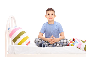 Cute little boy in pajamas sitting on a bed
