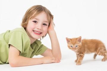 Portrait of smiling boy lying by kitten