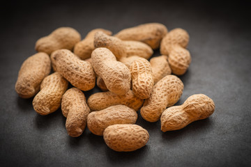 Natural looking roasted peanuts on a dark background.
