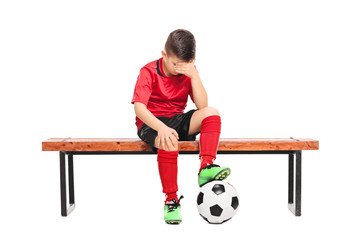 Sad kid in soccer uniform sitting on a bench