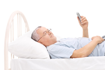 Senior watching something on his cell phone in bed