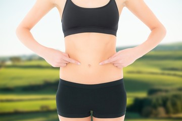 Fit woman with hands on stomach