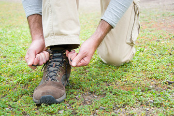 man hiking doing the knot shoes