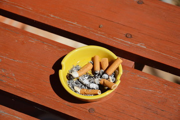 yellow ashtray on wood board