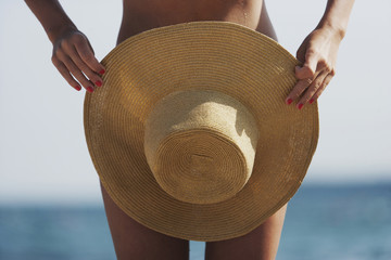 Woman holding summer hat in front of her tanned body